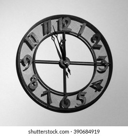 Old fashioned analog metal clock hanging on a wall, approaching the noon (or midnight) hour