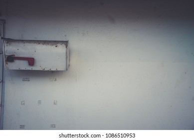 Old fashioned background with a mailbox and a white wall