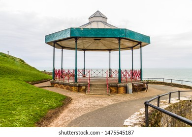 Old fashioned bandstand, sea behind it.