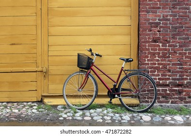 Old fashioned bicycle leaning against red brick wall and wooden gate (with place for your text) on a countryside street at summer day.