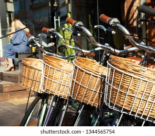 Old fashioned bicycles with wicker basket in front of bicycle shop in Tel Aviv, Israel. At background young blonde stylish business woman sitting at sunlight and using smartphone. Urban scene.