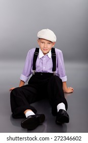 Old fashioned boy sitting and looking to the camera on gray background