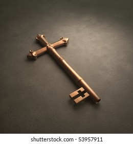 An old fashioned brass key laying on white surface shaped like a cross
