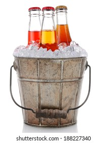 An old fashioned bucket filled with ice and soda bottles. Three different pop bottles are represented, strawberry cola and vanilla cream. Vertical format on a white background with reflection.