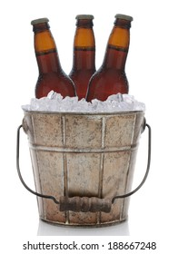 An old fashioned bucket filled with ice and beer bottles. Three brown bottles of beer are represented in vertical format on a white background with reflection.