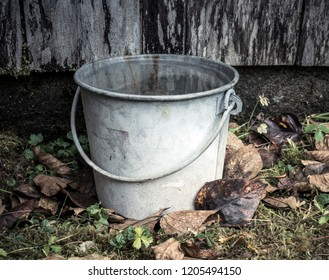 Old fashioned bucket sitting on the ground by an old wooden building with fall leaves.