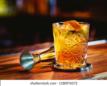 Old fashioned cocktail and beaker on the bar counter