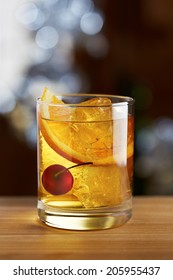 Old fashioned cocktail with a cherry on fancy background