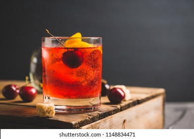Old fashioned cocktail with cherry and orange peel. Selective focus.