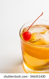 Old fashioned cocktail with cherry and orange peel