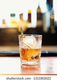 Old Fashioned cocktail drink with ice on bar disk with blurry bar and bottle background
