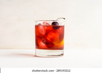Old fashioned cocktail on white wooden background