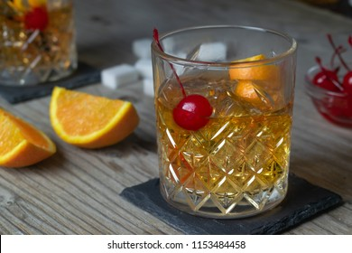 Old Fashioned Cocktail On Wooden Background with Orange Slices and Cherry