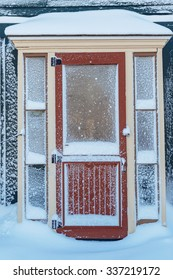 Old fashioned door and screen door after a snowfall.