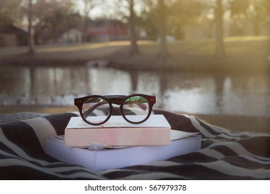 old fashioned eye glasses on books with black and white cloth and blurry lake background, filtered tone