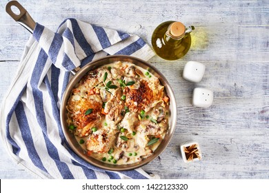 Old fashioned french dish chicken fricassee of fried chicken pieces simmered in cream sauce with vegetables: peas and carrot, garnished with sage on top, on a metal skillet on a white wooden table