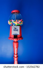 An old fashioned gumball machine against a colorful blue background, vertical.