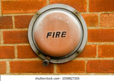 An old fashioned hand operated fire alarm bell fixed the brick wall of the exterior of a building.