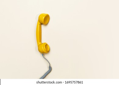 Old fashioned handset on beige color background. Modern retro style. New old technology. Copy space. Concept of Color of the Year 2021 with bright illuminating yellow and gray colours.