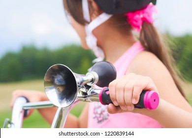 Old fashioned horn with chrome trumpet and black rubber bulb close-up mounted on a children's bike. Little girl in a pink protective helmet and pink t-shirt in the background.