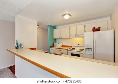 Old fashioned kitchen interior of American Apartment Condominium. White appliances , cabinets and long bar stand. Northwest, USA
