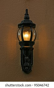 An old fashioned lamppost on a stucco wall