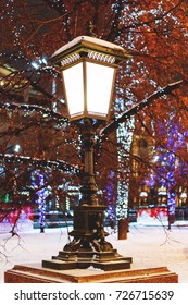 Old fashioned lantern on street. Trees are decorated for New Year and Christmas celebration. Moscow, Russia.