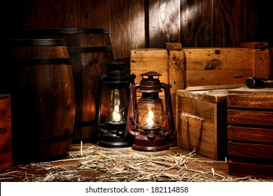 Old fashioned light kerosene lantern style oil lamps in antique shipping warehouse stockroom with vintage wooden crates containers and ancient storage boxes near retro whiskey transportation barrels