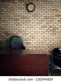 Old fashioned office interior, wooden working table in front of red brick wall and round clock, vintage style. Image captured by smartphone