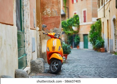 Old fashioned orange motorbike on a street of Trastevere district, Rome, Lazio, Italy