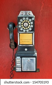 An old fashioned pay phone against a red background