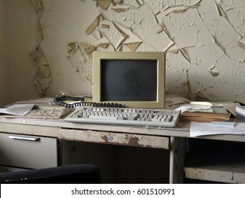 Old fashioned personal computer and keyboard on a desk in front of a wall that is peeling.