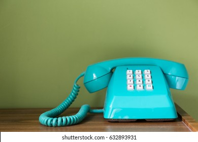 Old fashioned plastic telephone on a wooden desk with green wall.