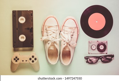 Old fashioned pop culture attributes from 80s on mint color background. Old sneakers, gamepad, audio cassette, videotape, vinyl plates, 3d glasses. Minimalism, top view
