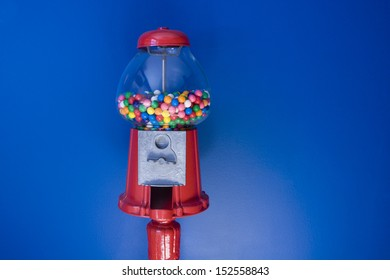 An old fashioned red gumball machine against a colorful blue background.