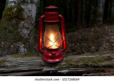 Old fashioned red oil lamp sitting on a log