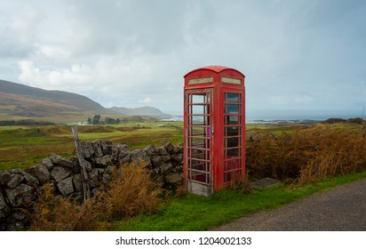 Old fashioned red telephone box in rural crofting township in the Scottish Highlands with the Isle of Eigg in the background.Red telephone boxes were widely used prior to modern technology. Horizontal