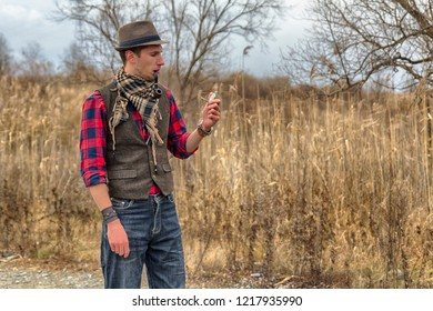 Old fashioned retro steampunk man in hat, wool vest, scarf with pocket watch in hand and smoking pipe in mouth. HDR image