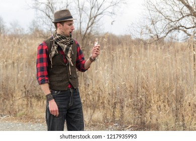Old fashioned retro steampunk man in hat, wool vest, scarf with pocket watch in hand and smoking pipe in mouth