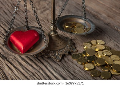 Old fashioned scale showing the advantage of love over money. Heart-shaped chocolate on one side of the scale, and coins on the other. Valentine's day concept.