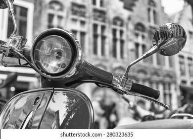 Old fashioned scooter in city center, black and white view.