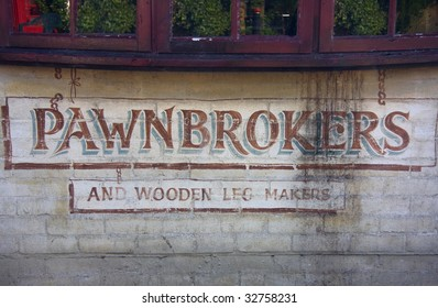 Old fashioned sign advertising a Pawnbroker and makers of wooden legs