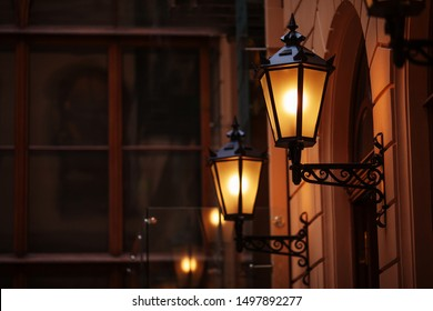 Old fashioned street lamp at night. Brightly lit street lamps at sunset. Decorative lamps. Magic lamp with a warm yellow light in the city twilight. Copy space