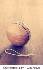 An old fashioned style wooden yoyo a retro childhood concept antique filter applied to image