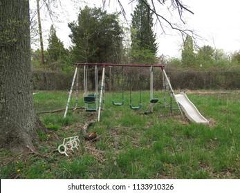 Old fashioned swing set on abandoned property.