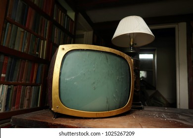 Old fashioned television set in front of a lamp. Natural light. Darkness surrounding.