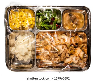 Old fashioned Thanksgiving TV dinner on metal tray covered in plastic