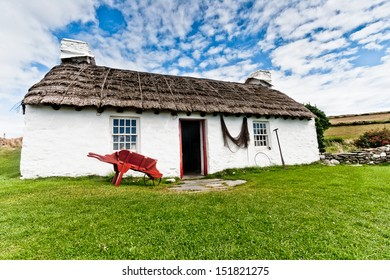 Old fashioned thatched crofter's cottage at Cregneash in the Isle of Man with red wooden wheelbarrow, fishing net and agricultural tool in the foreground with green grass and a blue sky.