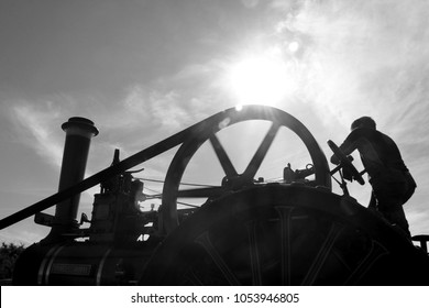 Old fashioned threshing machine and farm worker in monochrome