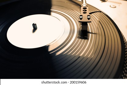 Old fashioned turntable playing a track from black vinyl in golden light.